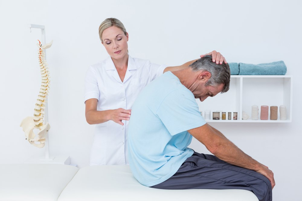 a chiropractor examines a patient's spine